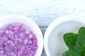 Aromatherapy treatment bowl with flowers and perfumed water on wooden background — Stock Photo
