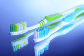 зубные щетки на синем фоне — Стоковое фото