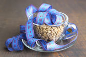 Raw green coffee beans in glass cup and measuring tape, on color wooden background. Concept of weight loss — Stok fotoğraf