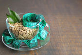 Raw green coffee beans in glass cup and measuring tape, on color wooden background. Concept of weight loss — Foto de Stock