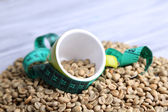 Raw green coffee beans and measuring tape, on color wooden background. Concept of weight loss — Foto de Stock