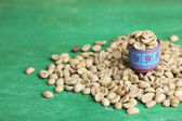 Raw green coffee beans and measuring tape, on color wooden background. Concept of weight loss — Stock fotografie