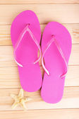 Bright flip-flops on wooden background — Stock Photo