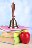Gold school bell with school supplies on table on bright background — Stock Photo