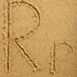 Alphabet letter written on wet beach sand — Stock Photo