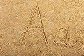 Alfabet list napisany na mokry piasek plaża — Zdjęcie stockowe