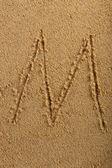 Alphabet letter written on wet beach sand — Stock Photo