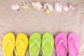 Bright flip-flops on sand, close up — Stock Photo