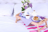 Light breakfast and beautiful bouquet on bed — Stock Photo