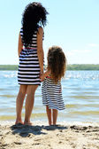 Happy mom and daughter on the beach — Stock Photo