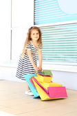 Happy little girl with shop bags, outdoors — Stock Photo