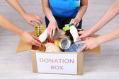 People makes foodstuffs out of donation box on grey background — Stock Photo