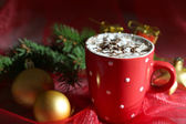 Hot chocolate with cream in color mug, on table, on Christmas decorations background — Stock Photo