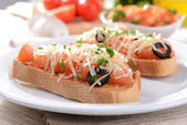Delicious bruschetta with tomatoes on plate on table close-up — Stockfoto
