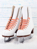Figure skates on wooden background — Stock Photo