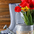 Composition of colorful tulips in watering can and rain boots on bright background — Stock Photo