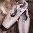 Ballet pointe shoes on dark  wooden background — Stock Photo #46589233