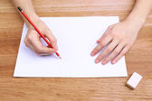 Human hands with pencil writing on paper and erase rubber on wooden table background — Stock Photo