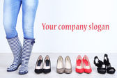Girl chooses shoes in room on grey background — Stock Photo