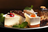 Assortment of pieces of cake, on dark background — Foto de Stock