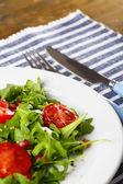 Green salad made with  arugula, tomatoes and sesame  on plate, on wooden background — Stockfoto