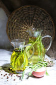 Essential Oil with rosemary in glass jug, on dark background — Foto de Stock
