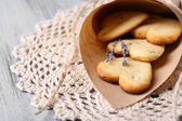 Lavender cookies in paper bag, on color wooden background — Foto de Stock