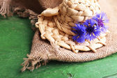 Small straw hat with cornflowers on wooden background — Stock Photo