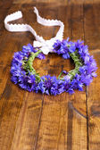 Fresh cornflower wreath on wooden background — Stock Photo