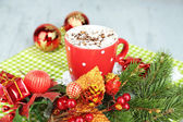 Hot chocolate with cream in color mug, on napkin, on Christmas decorations background — Stock Photo