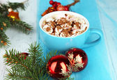 Hot chocolate with cream in color mugs, on table, on Christmas decorations background — Stock Photo