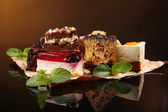 Assortment of pieces of cake, on dark background — Stock Photo