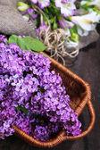 Beautiful lilac flowers in wicker basket on wooden background — Foto Stock