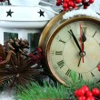 Clock with fir branches and Christmas decorations on table on wooden background — Stock Photo #46931345