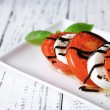 Caprese salad with mozarella cheese, tomatoes and basil on plate, on wooden table background — Stock Photo #46931933