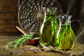 Essential Oil with rosemary in glass jugs, on wooden background — Foto de Stock