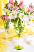 Freesias in glasses on table on fabric background — Stock Photo