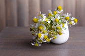 Beautiful daisies flowers in vase on table on grey background — Stock Photo