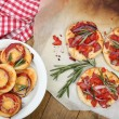 Small pizzas on baking paper close up — Stock Photo