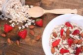 Cereal saudável com morango e nozes na mesa de madeira — Fotografia Stock
