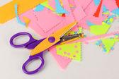 Kleurrijke zigzag schaar met papier van de kleur op wit wordt geïsoleerd — Stockfoto