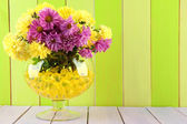 Beautiful flowers in vase with hydrogel on table on wooden background — Stock Photo