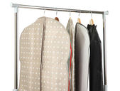 Clothes in cases for storing on hangers, on gray background — Stockfoto