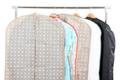 Clothes in cases for storing on hangers, on gray background — Stock Photo