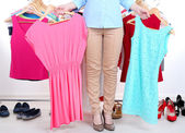 Young woman choose clothes near rack with hangers — Stock Photo
