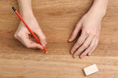 Human hands with pencil and erase rubber on wooden table background — Stock Photo