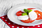 Caprese salad with mozarella cheese, tomatoes and basil on plate, on wooden table background — Stock Photo
