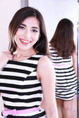 Beautiful girl trying dress near mirror in room — Stock Photo