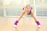 Sportiga kvinnan gör övningar i gym — Stockfoto