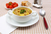 Tasty soup in saucepan on tablecloth, close up — Stock Photo
